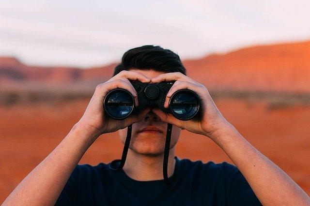 Chlapec v modrom tričku pozerá do ďalekohľadu